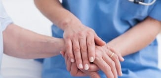 nurse holding the hand of a patient