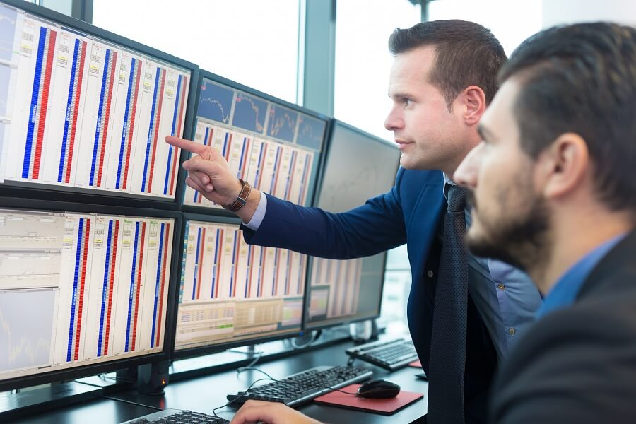 businessmen looking at some graphs on a computer screen