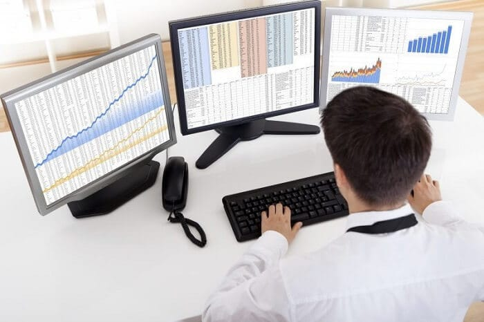 stock broker working on two computer monitors