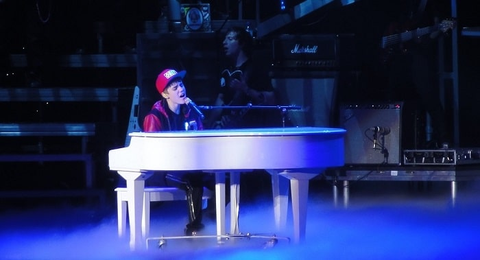 a younger justin bieber playing the piano