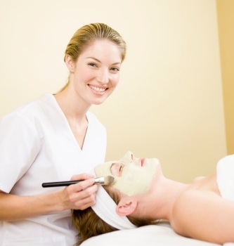Esthetician providing a facial treatment to a client