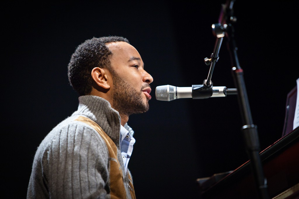 John Legend Singing playing piano against black background