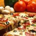 a tasty hot and huge pizza pie with a lot of toppings on it and some vegetables on the side
