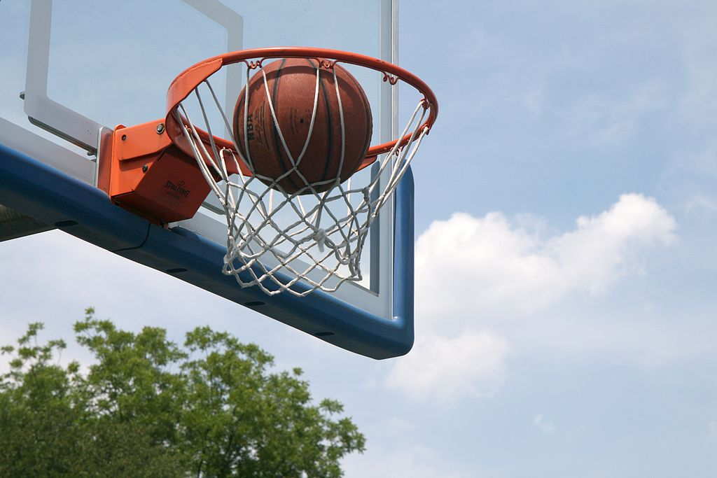 Basketball Ball about to fall through the hoop at a court that shows kinetic energy exerted by the player