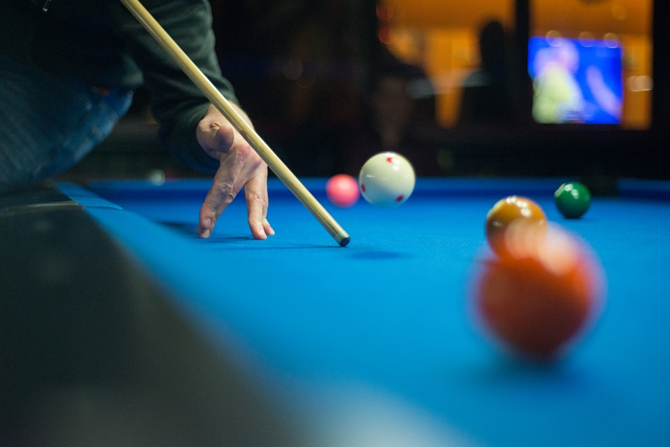 Billiard Player Successfully making a Jump Shot of a Billiard Ball that shows kinetic energy exerted