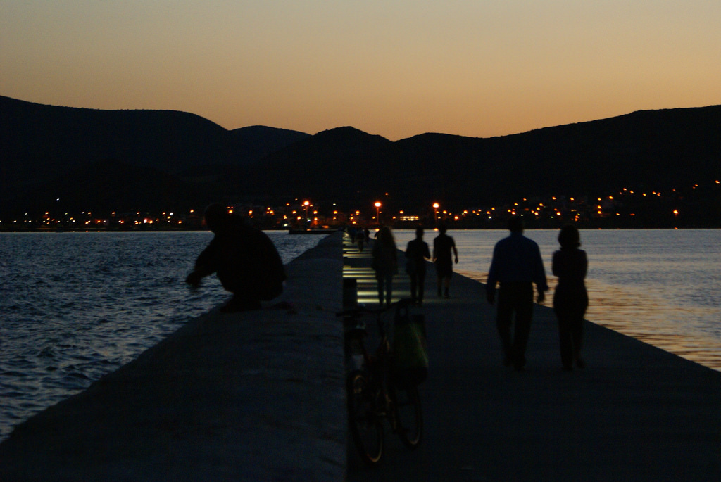 Sunset on a Bay showing an alone man, a married couple, and a group of three towards the discussion of Psychology vs. Sociology