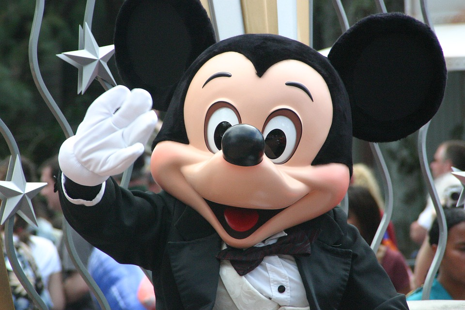 mickey mouse happily waving at the people