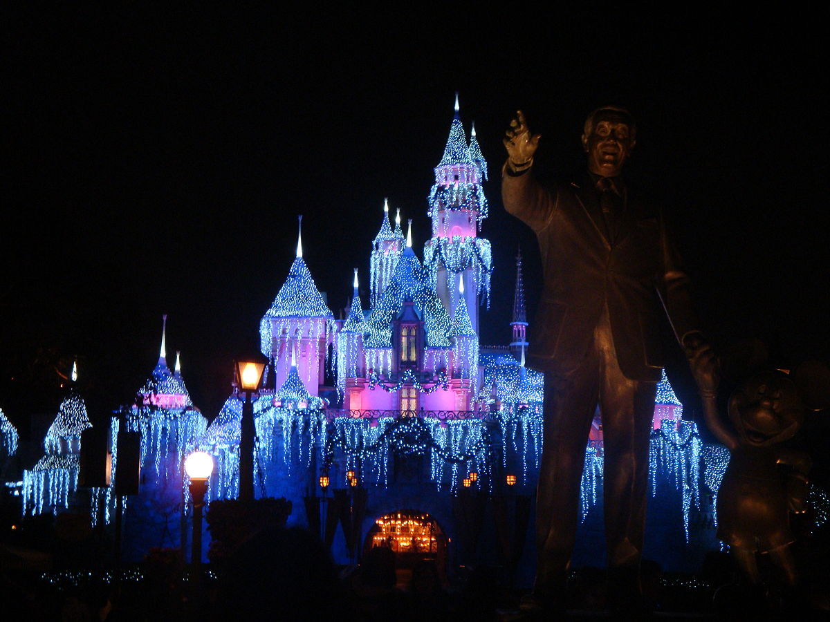 winter in disney showing walt disney statue in foreground and decked out castle with holiday lights in background