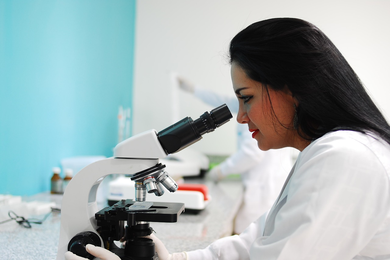 Woman looking her test subject using microscope
