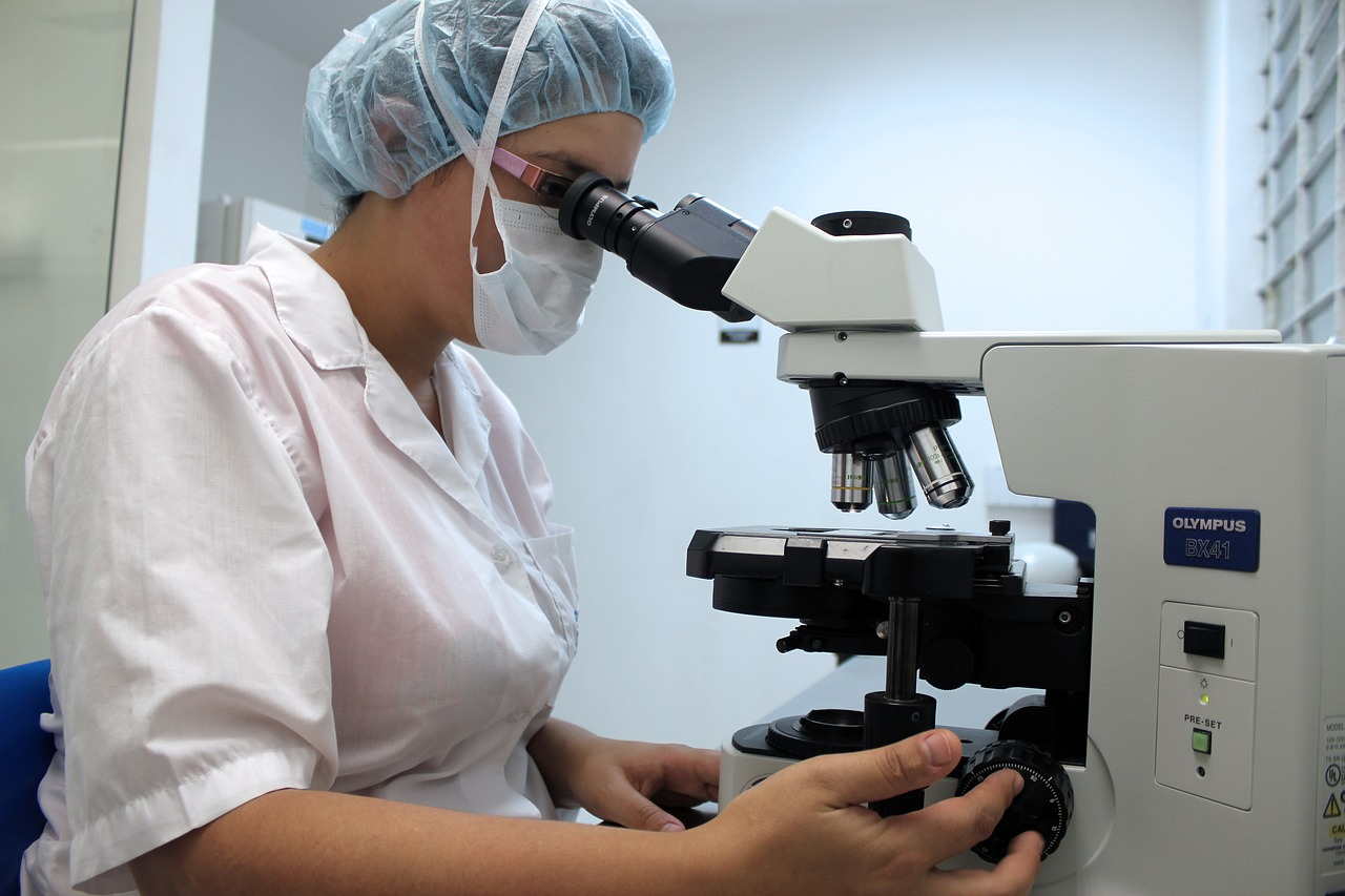 A nurse using an microscope